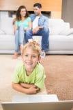 Счастливый мальчик используя компьтер-книжку на половике при родители сидя софа Стоковые Изображения RF