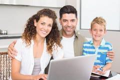 Счастливый мальчик используя компьтер-книжку с родителями на таблице Стоковые Изображения