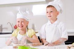 Счастливый мальчик и девушка варя в кухне Стоковая Фотография