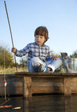 Счастливый мальчик идет удить на реке с любимчиком, детьми одним и набором стоковое изображение