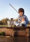 Счастливый мальчик идет удить на реке с любимчиком, детьми одним и набором Стоковая Фотография