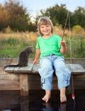 Счастливый мальчик идет удить на реке с любимчиком, детьми одним и набором Стоковые Изображения RF