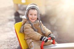 Счастливый мальчик отбрасывая на качании Стоковые Изображения