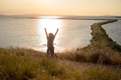 Счастливый мальчик при открытые оружия ехать его велосипед на заходе солнца Стоковое Изображение RF