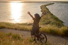 Счастливый мальчик при открытые оружия ехать его велосипед на заходе солнца Стоковая Фотография