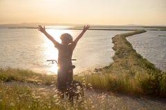Счастливый мальчик при открытые оружия ехать его велосипед на заходе солнца Стоковые Изображения
