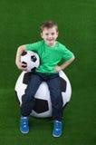 Счастливый мальчик сидя на футбольном мяче стоковое фото