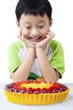 Счастливый мальчик смотря торт плодоовощ Стоковые Изображения