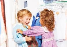 Счастливый мальчик с девушкой которая приспосабливает на его жилет в магазине стоковое фото