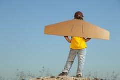 Счастливый мальчик с картонными коробками крылов против мечты неба мухы Стоковая Фотография RF