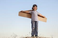 Счастливый мальчик с картонными коробками крылов против мечты неба мухы Стоковое фото RF