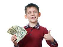 Счастливый мальчик с долларами и большие пальцы руки вверх показывать изолированный Стоковые Изображения
