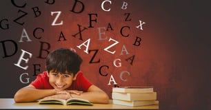 Счастливый мальчик с склонностью книги на таблице против писем летания стоковое изображение rf
