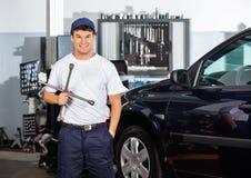 Счастливый механик держа ключ оправы на гараже Стоковые Изображения