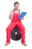 Счастливый механик держа ge доски сзажимом для бумаги и показывая как или большого пальца руки-вверх Стоковое Фото