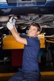 Счастливый механик работая под поднятым автомобилем стоковые изображения rf