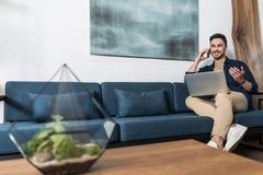 Счастливый моложавый парень работая в его живущей комнате Стоковое Изображение RF