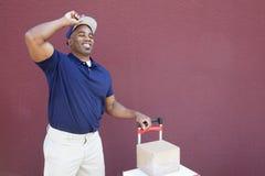 Счастливый молодой Афро-американский работник доставляющий покупки на дом стоя с handtruck над покрашенной предпосылкой Стоковая Фотография