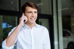 Счастливый молодой бизнесмен говоря на мобильном телефоне около делового центра Стоковые Изображения RF