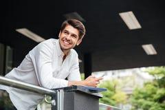 Счастливый молодой бизнесмен используя smartphone около делового центра Стоковое Изображение