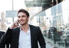Счастливый молодой бизнесмен идя около делового центра Стоковое Изображение