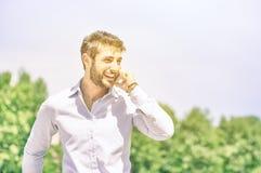 Счастливый молодой бизнесмен на парке при smartphone имея пролом стоковое фото
