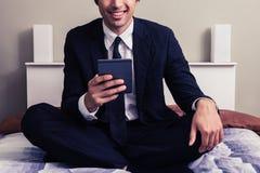 Счастливый молодой бизнесмен сидя в чтении кровати на таблетке Стоковые Изображения RF