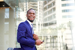Счастливый молодой бизнесмен стоя в городе Стоковая Фотография RF