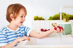 Счастливый молодой мальчик моя охапку сладостных вишен под водой из крана в кухне Стоковая Фотография