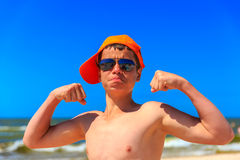Счастливый молодой мальчик на пляже моря демонстрирует бицепс Стоковая Фотография