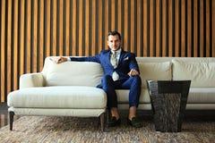 Счастливый молодой сидеть бизнесмена ослабил на софе на лобби гостиницы используя smartphon, ждать кто-то Стоковая Фотография RF