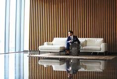 Счастливый молодой сидеть бизнесмена ослабил на софе на лобби гостиницы используя smartphon, ждать кто-то Стоковое фото RF