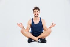 Счастливый молодой спортсмен сидя в представлении и усмехаться лотоса стоковая фотография rf