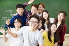 Счастливый молодой студент колледжа группы в классе стоковое фото