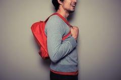 Счастливый молодой студент с красным рюкзаком стоковое фото