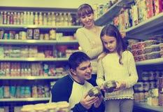 Счастливый молодой усмехаться parents при залуживанное приобретение маленькой девочки Стоковые Фотографии RF