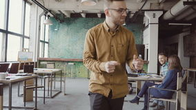 Счастливый молодой человек в жизнерадостном настроении идя через офис и танцевать шальные Бизнесмен приветствует с коллегами видеоматериал