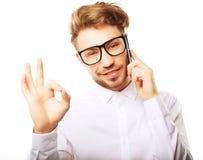 Счастливый молодой человек в рубашке показывать и усмехаясь пока говорящ дальше Стоковое фото RF