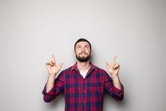 Счастливый молодой человек в рубашке указывая вверх и смотря вверх Изолированная серая предпосылка Стоковое фото RF