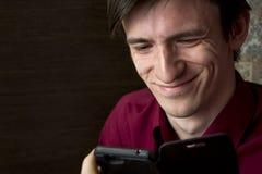 Счастливый молодой человек в фиолетовой рубашке смотря черный smartphone, усмехаясь обширно Стоковые Фотографии RF