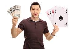 Счастливый молодой человек держа пачки денег и 4 тузов Стоковое Фото
