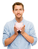 Счастливый молодой человек кладя деньги в изолированную копилку на белизне Стоковое Фото