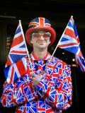 Счастливый молодой человек развевая флаг Великобритании Стоковое Фото