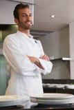 Счастливый молодой шеф-повар стоя с оружиями пересек за счетчиком Стоковая Фотография
