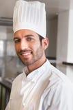 Счастливый молодой шеф-повар усмехаясь на камере Стоковая Фотография