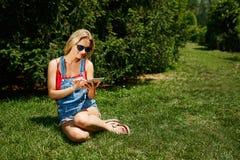 Счастливый молодой blondy ПК таблетки пользы студента колледжа женщины сидит на gr Стоковые Изображения