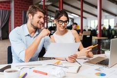 Счастливый молодые бизнесмен и женщина работая совместно в офисе Стоковая Фотография