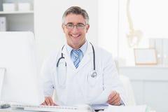 Счастливый мужской доктор рассматривая документы на таблице Стоковое фото RF