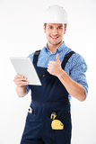Счастливый мужской построитель показывая большой палец руки вверх и держа таблетку ПК стоковая фотография rf