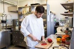 Счастливый мужской шеф-повар варя еду на кухне ресторана Стоковая Фотография